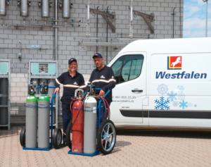 Mitarbeiter mit Flaschen mit integriertem Druckminderer und Transportwagen